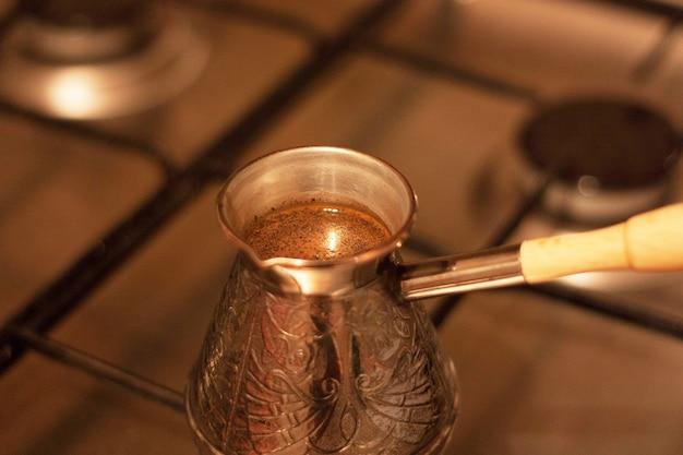 Pyszna czarna kawa parzona na kuchence gazowej w turku. robienie kawy w domu. ożywczy napój na poranek