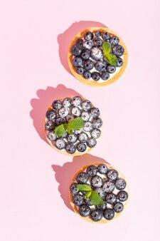 Pyszna deserowa tarta jagodowa ze świeżymi jagodami na różowym słodkim smacznym serniku ciasto jagodowe francuskie ...