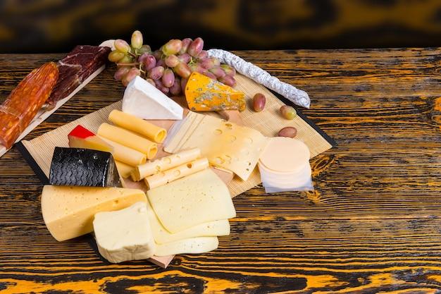 Pyszna deska serów na stole w formie bufetu z dużym wyborem różnych serów w klinach wyświetlanych ze świeżymi winogronami, wysoki kąt widzenia z copyspace na drewnianym stole