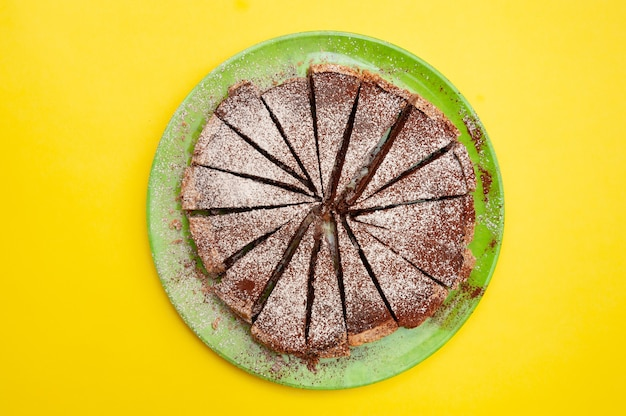 Pyszna domowa tarta czekoladowa z cukrem pudrem na żółtym tle