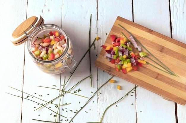 Pyszna fasola sałatkowa w słoiku i deska do krojenia