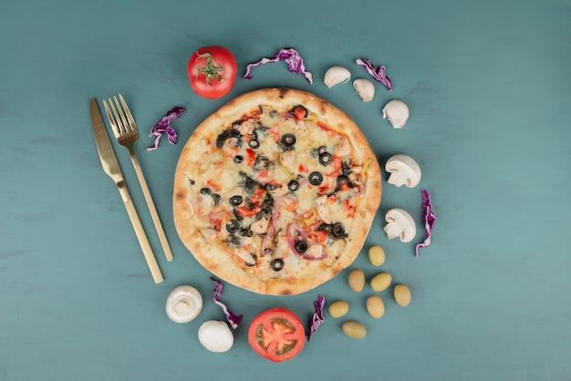 Pyszna gorąca pizza z oliwkami, pieczarkami i pomidorami na niebieskiej powierzchni.