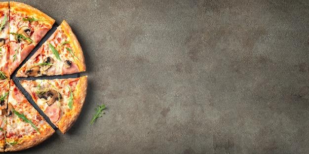 Pyszna gorąca pizza z szynką i pieczarkami.