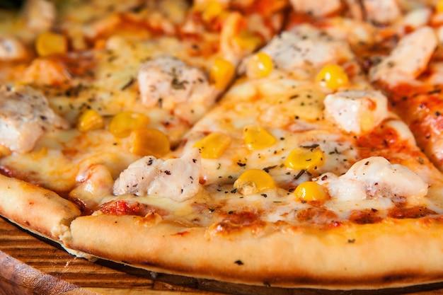 Pyszna gorąca włoska pizza w plasterkach i podawana na drewnianym półmisku cateringowym zbliżenie.