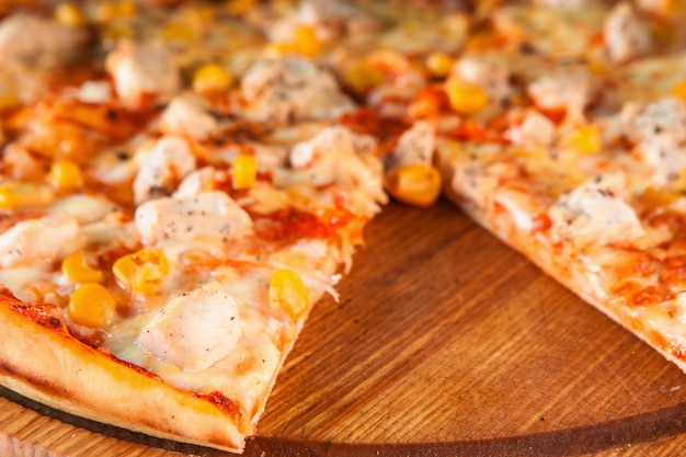 Pyszna gorąca włoska pizza w plasterkach i podawana na drewnianym półmisku gastronomicznym z widokiem na pokrojony kawałek.