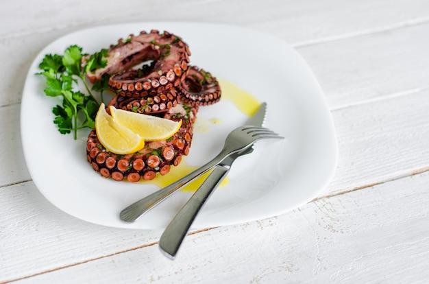Pyszna gotowana ośmiornica z cytryną, natką pietruszki i sosem sałatkowym na białym talerzu. tradycyjne śródziemnomorskie owoce morza