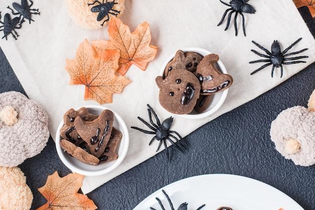 Pyszna halloweenowa uczta - pierniki z polewą czekoladową w miseczkach na stole z dyniami i liśćmi. tradycyjne świętowanie, słodkie jedzenie. widok z góry