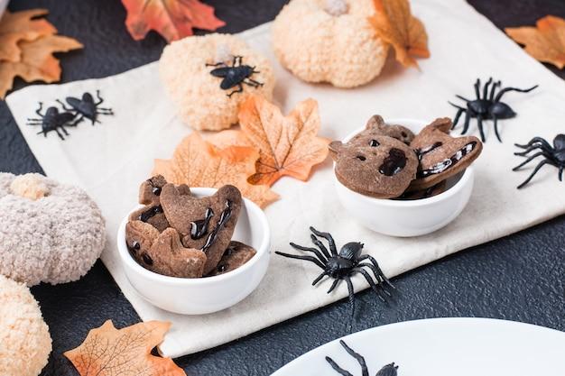 Pyszna halloweenowa uczta - pierniki z polewą czekoladową w miseczkach na stole z dyniami i liśćmi. tradycyjne świętowanie, słodkie jedzenie.