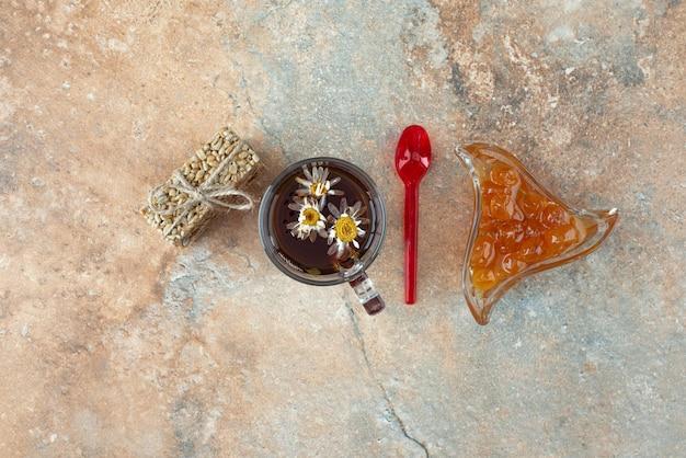 Pyszna herbata rumiankowa z kawałkami orzechów ziemnych i dżemem.