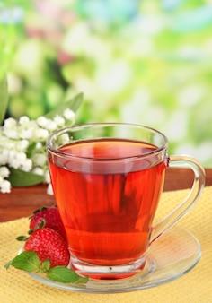 Pyszna herbata truskawkowa na stole na jasnym tle