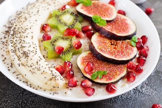 Pyszna i zdrowa owsianka z figami, kiwi, granatem, bananem i nasionami chia. zdrowe śniadanie. odpowiednie odżywianie.
