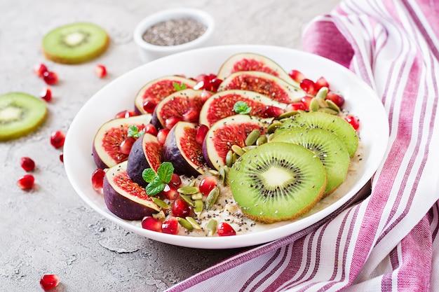 Pyszna i zdrowa owsianka z figami, kiwi i granatem. zdrowe śniadanie. jedzenie fitness. odpowiednie odżywianie.