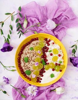 Pyszna i zdrowa owsianka z winogronami, jogurtem i twarogiem. zdrowe śniadanie. jedzenie fitness. odpowiednie odżywianie. leżał płasko. widok z góry.