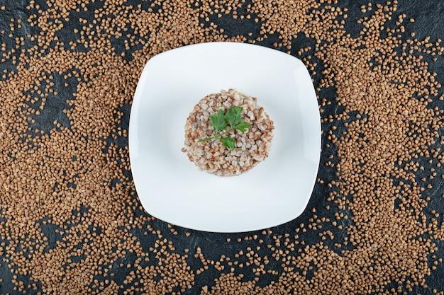 Pyszna kasza gryczana z zieleniną na białym talerzu.
