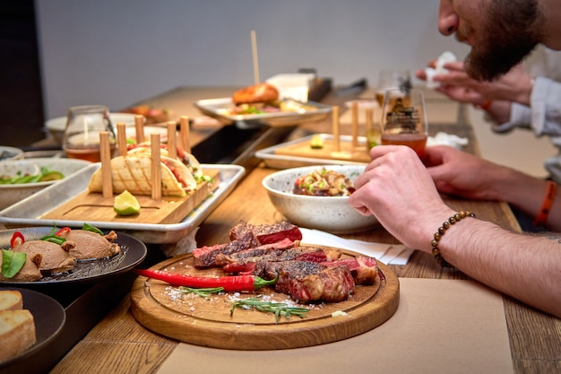 Pyszna kolacja w restauracji na drewnianym stole. smaczne jedzenie z piwem w menu kawiarni lub pubu. ludzie jedzący fast foody spędzający razem czas