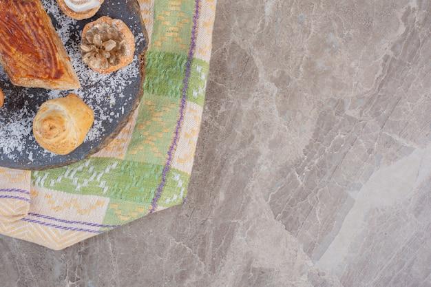 Pyszna kyata otoczona ciasteczkami zwieńczona lokum i szyszkami sosnowymi na marmurowej desce.