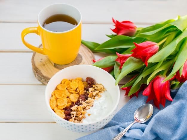 Pyszna miska jogurtu z płatkami kukurydzianymi, orzechami i dżemem na białym drewnianym stole. pojęcie zdrowego i ekologicznego odżywiania. tulipany z filiżanką herbaty i śniadaniem.