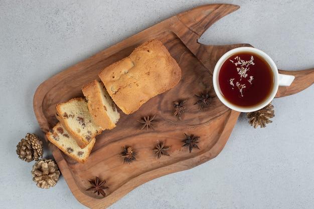 Pyszna muffinka z rodzynkami i filiżanką herbaty na drewnianej desce