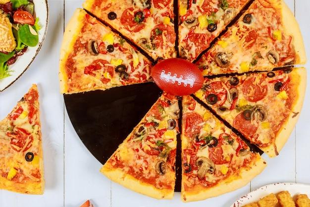 Pyszna najwyższa pizza na mecz futbolu amerykańskiego z piłką na wierzchu.