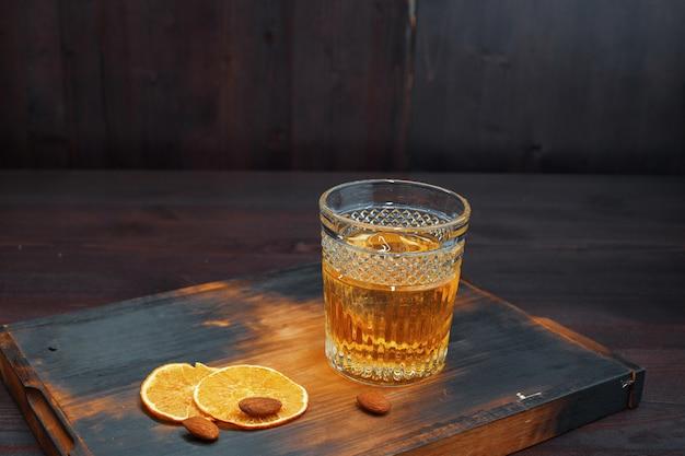 Pyszna, niesamowita szkocka whisky w kryształowym kieliszku ozdobiona plastrami świeżej pomarańczy stoi na zabytkowym drewnianym stole w pubie. mocny męski napój. weekend w barze