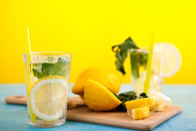 Pyszna organiczna woda detoksykująca z cytrynami na żółtym tle w niebieskiej drewnianej desce w stylu vintage