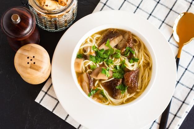 Pyszna pachnąca zupa z białych grzybów w misce na okrągłym drewnianym stojaku. widok z góry. czarne tło.