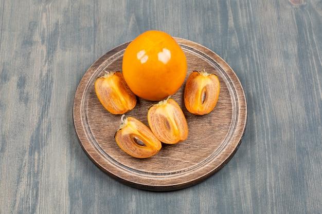 Pyszna persimmon w plasterkach na drewnianym talerzu