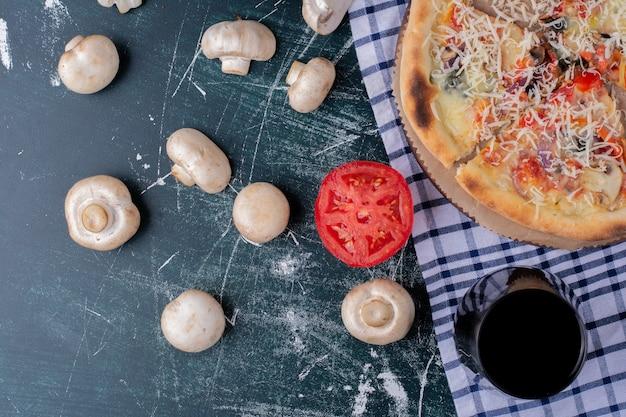 Pyszna pizza grzybowa z szklanką soku i świeżymi warzywami na marmurze.