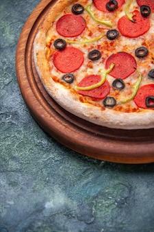 Pyszna pizza na drewnianej desce do krojenia po lewej stronie na izolowanej ciemnej powierzchni z wolną przestrzenią w widoku z bliska