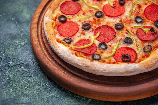 Pyszna pizza na drewnianej desce do krojenia po lewej stronie na izolowanej ciemnej powierzchni z wolną przestrzenią w zbliżeniu