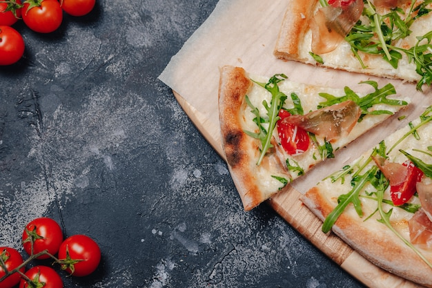 Pyszna pizza neapolitańska na pokładzie z pomidorami koktajlowymi, wolne miejsce na tekst
