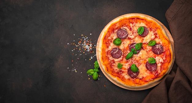 Pyszna pizza pepperoni, przyprawy, bazylia i lniana serwetka na brązowym tle.