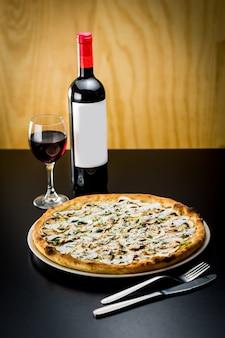 Pyszna pizza podawana z butelką i kieliszkiem czerwonego wina w restauracji