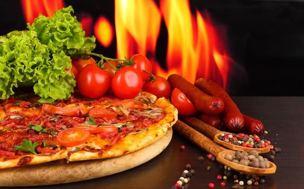 Pyszna pizza, salami, pomidory i przyprawy na drewnianym stole