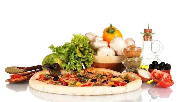 Pyszna pizza, warzywa, przyprawy i olej na białym tle