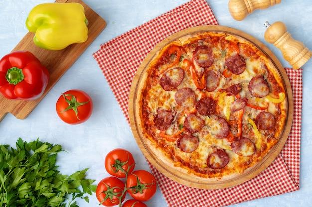 Pyszna pizza z kiełbasami na szarym tle widok z góry