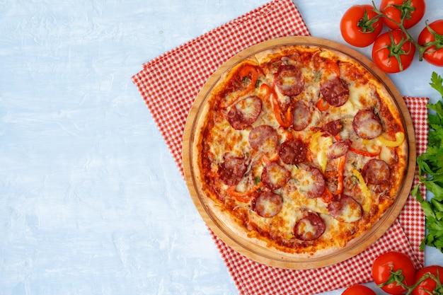 Pyszna pizza z kiełbasami na szarym tle