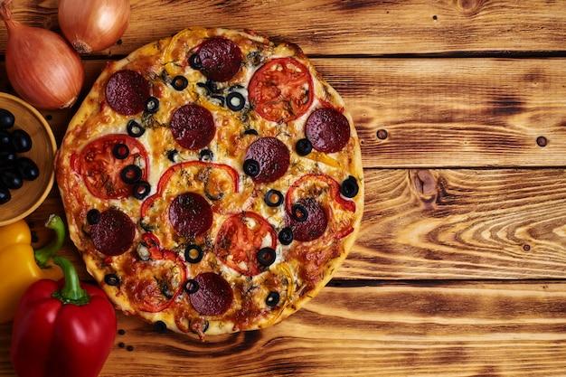 Pyszna pizza z salami, oliwkami, czerwoną papryką i pomidorem na drewnie. rustykalny. jedzenie. widok z góry. skopiuj miejsce