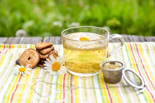 Pyszna poranna herbata w szklanej filiżance z rumiankiem.