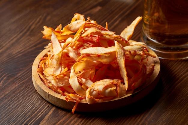 Pyszna przekąska do piwa - suszone i solone krążki kalmarów w drewnianym talerzu.