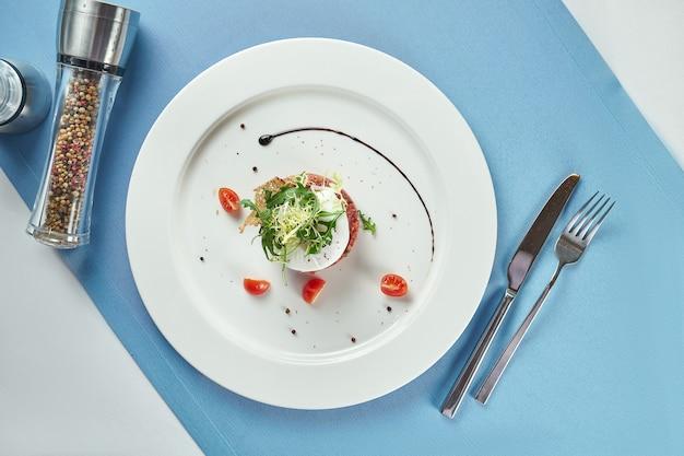 Pyszna przystawka - tatar wołowy z grzankami, jajkiem w koszulce i rukolą w białym talerzu na niebieskim obrusie