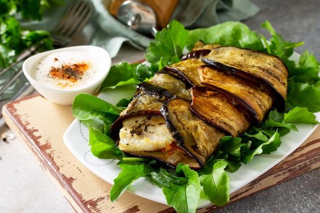 Pyszna ryba zapiekana z warzywami w bakłażanie grillowana na stole z kamienia lub łupka