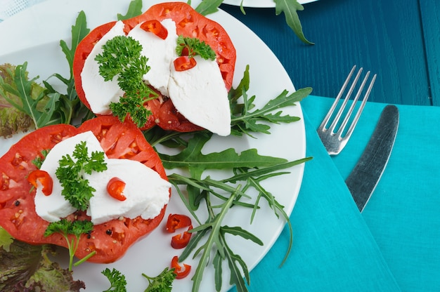 Pyszna sałatka caprese z mozzarellą, dojrzałymi pomidorami i świeżą rukolą.