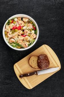 Pyszna sałatka z krewetkami, oliwkami, mozzarellą, pomidorami, sosem z oliwy i bułeczkami żytnimi