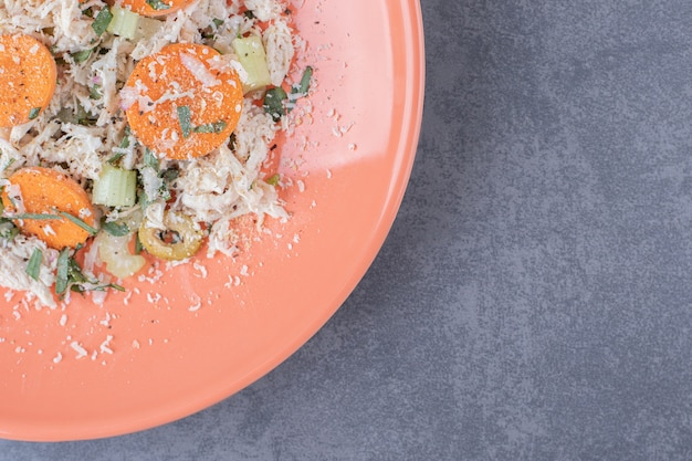 Pyszna sałatka z kurczaka na pomarańczowym talerzu.