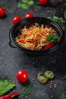 Pyszna sałatka z pomidorami, pieczonymi ziemniakami, pomidorami i świeżymi ziołami, świeża sałatka w menu restauracji fast food na ciemnym kamiennym stole. zdrowa opcja fast foodów.