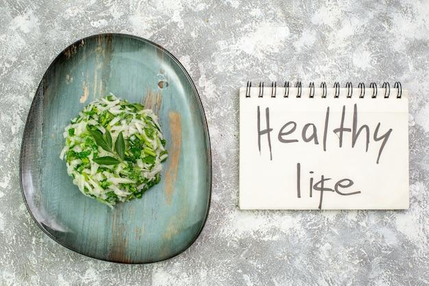 Pyszna sałatka z widokiem z góry składa się z zieleni i kapusty wewnątrz talerza