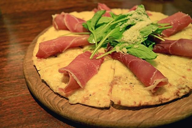 Pyszna serowa i chrupiąca pizza prosciutto rukola na drewnianym stole