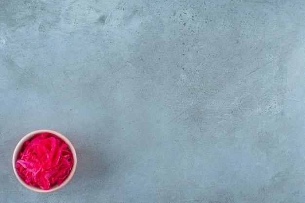 Pyszna sfermentowana czerwona kapusta leży w misce, na niebieskim stole.