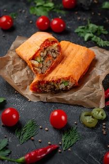 Pyszna shawarma i tacos w lawaszu serowym na ciemnym kamiennym stole. restauracja fast food. zdrowa opcja fast foodów. smaczne świeże zawijane kanapki z mięsem wołowym i warzywami, tradycyjne średnie